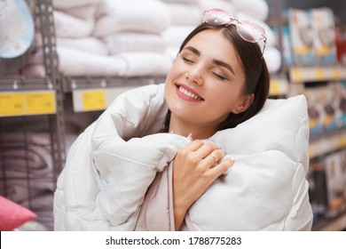 Close up of a happy beautiful woman enjoying being wrapped in warm cozy blanket while shopping for home goods