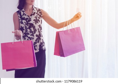Close up of happy Caucasian or young women with shopping bags. Woman holding shopping bags. Closeup images concept of woman standing shopping and holding vibrant color paper bags,