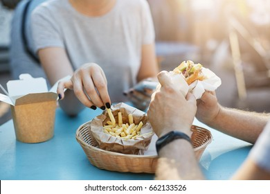 Close up of happy couple or friends coworkers having a burger and fries during lunchtime in a park on a sunny summer day. Junk food concept.