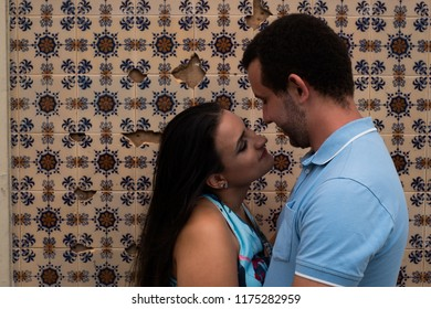 Close of a happy couple in front of portuguese and european tiles
