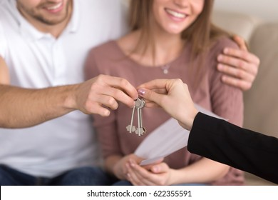 Close up of happy couple getting keys to their new house, hand of a female real estate agent giving apartment keys to a man sitting on sofa embracing his girlfriend, renting or buying home concept