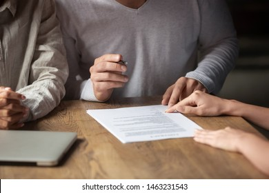 Close up of happy couple sign contract closing deal with real estate agent buying first property together, husband put signature on agreement finalize negotiation take loan or mortgage from banker