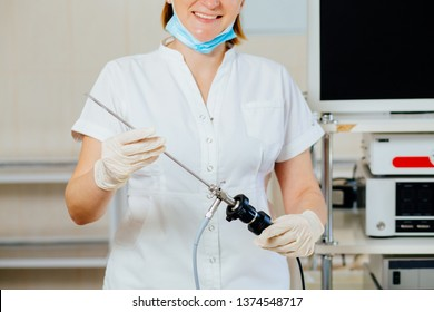 Close up of happy female surgeon in protective wear uniform, medical gloves hysteroscope for laparoscopy operation in empty operating room.