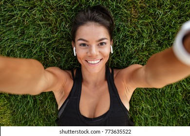 Close up of a happy fitness girl in earphones taking a selfie while laying on grass outdoors
