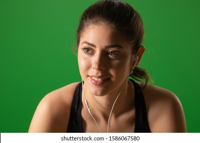 Close up of happy fitness woman listening to music on greenscreen. Portrait of Caucasian athlete wearing earbuds