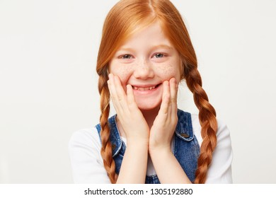 Close up of happy glad funny adorable girl with braided red hair in two long plaits, smiles and keeps palms on a face, dressed in jeans overall isolated on white background
