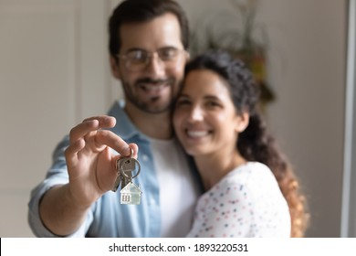 Close up happy husband hugging wife, satisfied customer holding keys from apartment, family purchase new house, real estate, first dwelling, celebrating moving day, relocation and mortgage concept