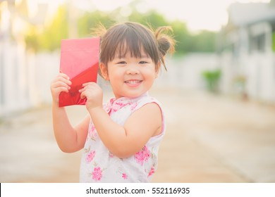 Close up Happy Little asian girl in chinese traditional dress laughing and smiling.Happy Concept.Chinese little girl happy face.happy chinese new year. smiling asian little girl holding red envelope