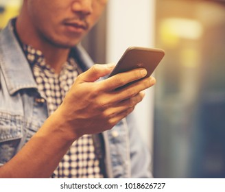 Close up  of happy male  in causual clothes holding smartphone on his right hand and using smartphone online Messaging,technology concept, copy space.