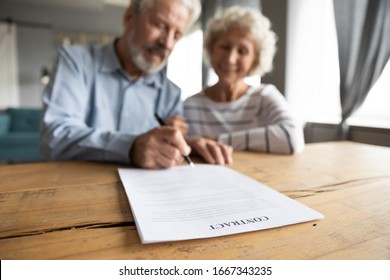Close up of happy mature 60s couple spouses clients close deal sign insurance contract with specialist, smiling middle-aged old husband and wife put signature make agreement, elderly care concept