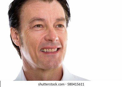 Close up of happy mature handsome man smiling while thinking and looking at distance