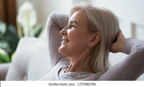 Close up of happy mature woman sit relax on sofa in living room breathing fresh air, smiling calm middle-aged female rest on couch at home daydreaming or enjoying leisure weekend, stress free concept