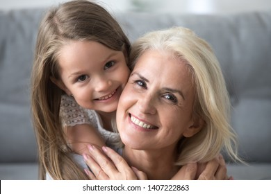 Close up happy middle aged woman hug little sweet girl looking at camera. Smiling grandma and preschool grandchild piggyback ride at home. Love and family tender relationships relative people concept