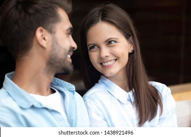 Close up of happy millennial couple look in eyes reconciled after fight or quarrel, smiling young husband and wife make peace show love and support, save marriage after family misunderstanding
