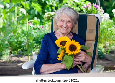 Close up Happy Old Lady in Blue Dress  Sitting on a Chair at the Garden, Holding Fresh Sunflowers While Looking at the Camera.