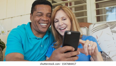 Close up of happy older couple sitting on porch and using smartphone together. African American and Caucasian husband and wife looking at cell phone on sunny day outside home