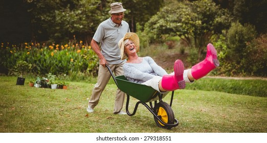 Close up of happy senior couple playing with a wheelbarrow in a sunny day