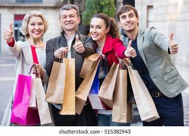 Close up of happy  smiling tourists with purchases on European city street
