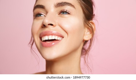 Close up of happy smiling woman face with white teeth, nude lip-gloss and natural no-makeup look, showing clean hydrated skin without blemishes, standing on pink background.