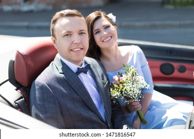 close up of Happy wedding couple sitting in cabriolet car, beautiful smiling bride and groom