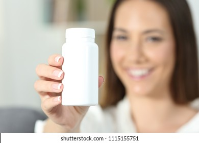 Close up of a happy woman hand showing a blank medicine bottle of pills