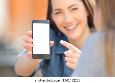 Close up of a happy woman hand showing a blank smart phone screen to a friend in the street