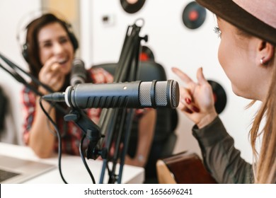 Close up of a happy woman singer performing at radio program while making podcast recording for online show, playing guitar