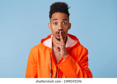 Close up of happy young african american dark skinned man in orange rain coat, tells secret information, demonstrates hush gesture, asks to keep quiet isolated over blue background.