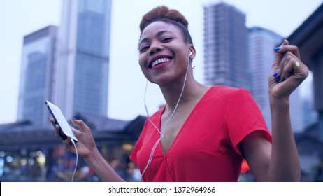 Close up of happy young African woman in red dress enjoying music dancing in the street. Joyful black young woman holding mobile phone listening to music wear earphone at Asian urban background.
