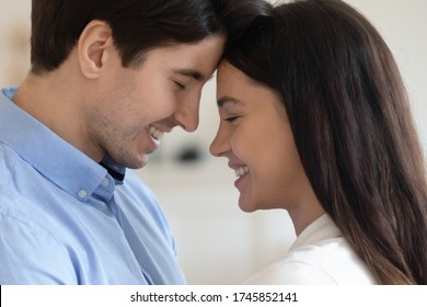 Close up of happy young caucasian couple look in eyes touch forehead enjoy tender romantic intimate moment together, smiling millennial man and woman lovers show affection and love in relationships