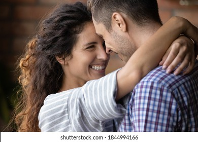 Close up of happy young Caucasian couple hug and cuddle enjoy tender close romantic moment together. Smiling millennial man and woman embrace show love and care in relationship. Marriage concept.