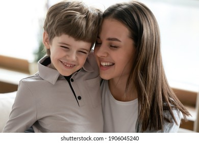 Close up of happy young Caucasian mother hold in arms hug smiling cute little son enjoy family weekend at home together. Caring mom embrace small boy child, show love, have tender sweet close moment.