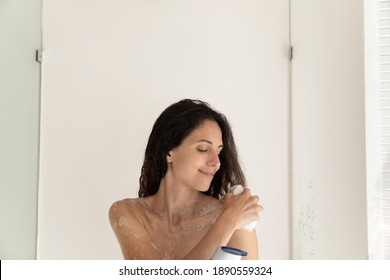 Close up of happy young Caucasian woman take shower use organic natural beauty product for daily use. Smiling lady wash clean in home bathroom with foamy gel or soap. Hygiene, body care concept.