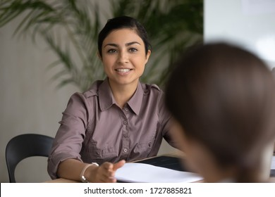 Close up happy young indian ethnic businesswoman talking about finance business project. Smiling diverse attractive female leader discussing sales presentation with workers in boardroom at meeting. - Shutterstock ID 1727885821