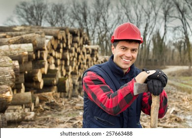 Close up of happy young lumberjack with ax beside cut trunks in forest