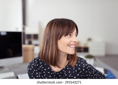 Close up Happy Young Office Woman with Brown Hair, Sitting at her Table While Looking to the Right of the Frame.