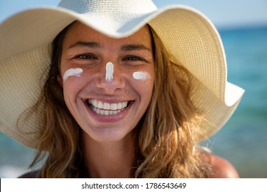Close up of happy young smiling woman with straw hat and sunscreen or sun tanning lotion on her face to take care and protect skin on a seaside beach during holidays vacation.