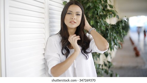 Close up of a happy young woman leaning on the wall while looking at the camera