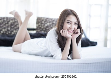Close up of a happy young woman smile while lying on the bed at home , model is a asian girl