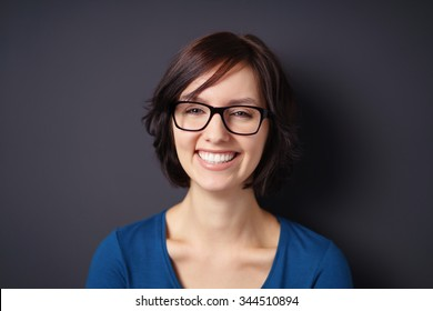 Close up Happy Young Woman, Wearing Eyeglasses, Showing Toothy Smile at the Camera Against Gray Wall Background.