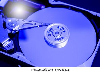 Close up hard disk's internal mechanism hardware. Detail of writing/reading . Blue Toned Image