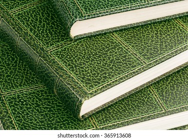 close up of hardcover books with green leather