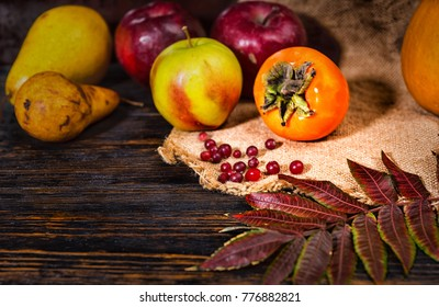 Close up of harvest of apples, pear, rowan and pumpkins lying on linen cloth near leaves. Mockup for seasonal offers and holiday post card