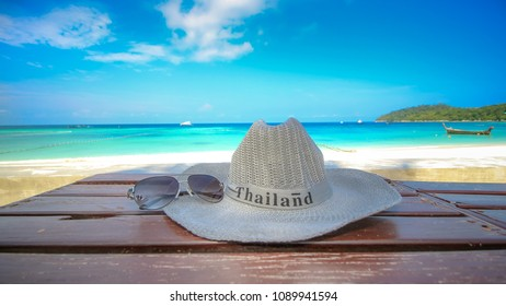 "Close up hat have wording ""Thailand"" and Sunglass on beautiful beach with nice sea sand and clear bluesky background.Concept travelers in beautiful nature landscape koh lipe Thailand.Landscape hdr."