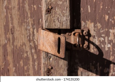 A close up of a hatch lock on an old wood door with peeling paint.