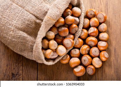 close up of hazelnuts on wooden table, top view