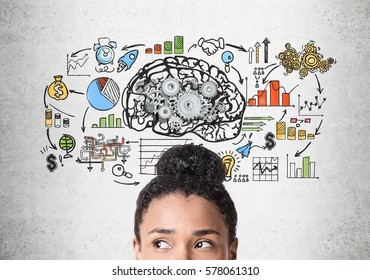 Close up of a head of an African American woman standing near a concrete wall with a brain sketch with gears and a startup drawing.