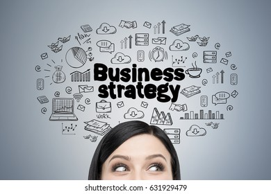 Close up of a head of a black haired woman standing near a gray wall with a business strategy sketch drawn on it.