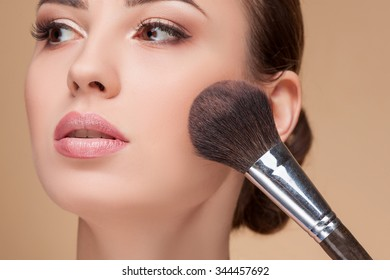 Close up of head of cheerful girl attending beauty shop. The visagiste is applying powder on female check with a brush. The lady is looking forward with serenity