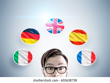 Close up of a head of a hipster guy in glasses against a gray wall with European country flags drawn on it.